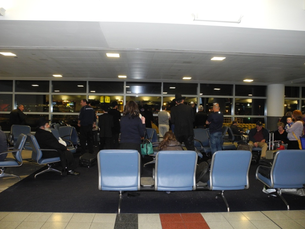 People praying in the boarding area by the windows.