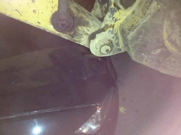 Close up of backhoe resting on (aka smashing) BMW hood.