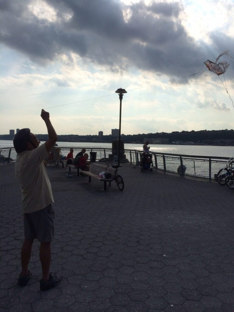 Chinese man flying a homemade kite.