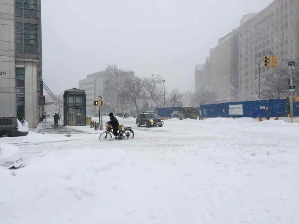 Delivery man pushing his bicycle through the snow.