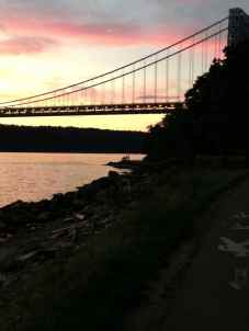 People on an outcropping of rock looking at the George Washington Bridge