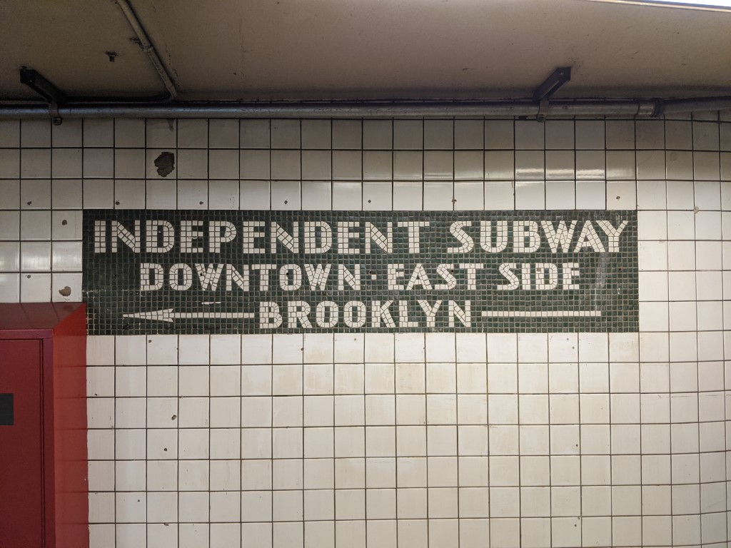 Image of old Independent Subway Downtown-East Side-Brooklyn tile sign at 6th Ave L/PATH station in Manhattan.