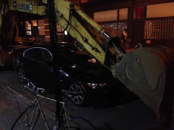 BMW with backhoe crushing hood