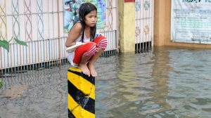 Filipina girl crouches on cement pillar to avoid flood waters
