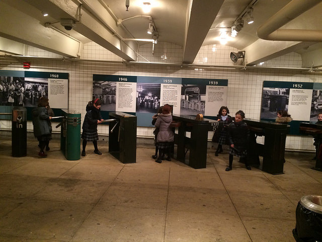 Students on a field trip trying out old subway turnstiles.