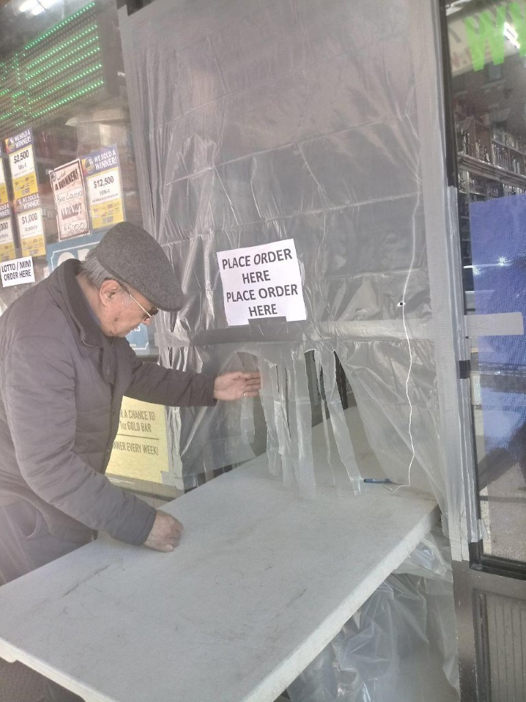 Plastic shielding and a sign at the entrance of a liquor shop requiring customers to remain outside