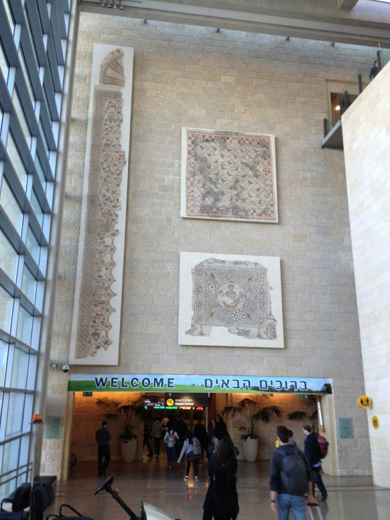 Mosaics on the wall, heading into the customs/border control area.