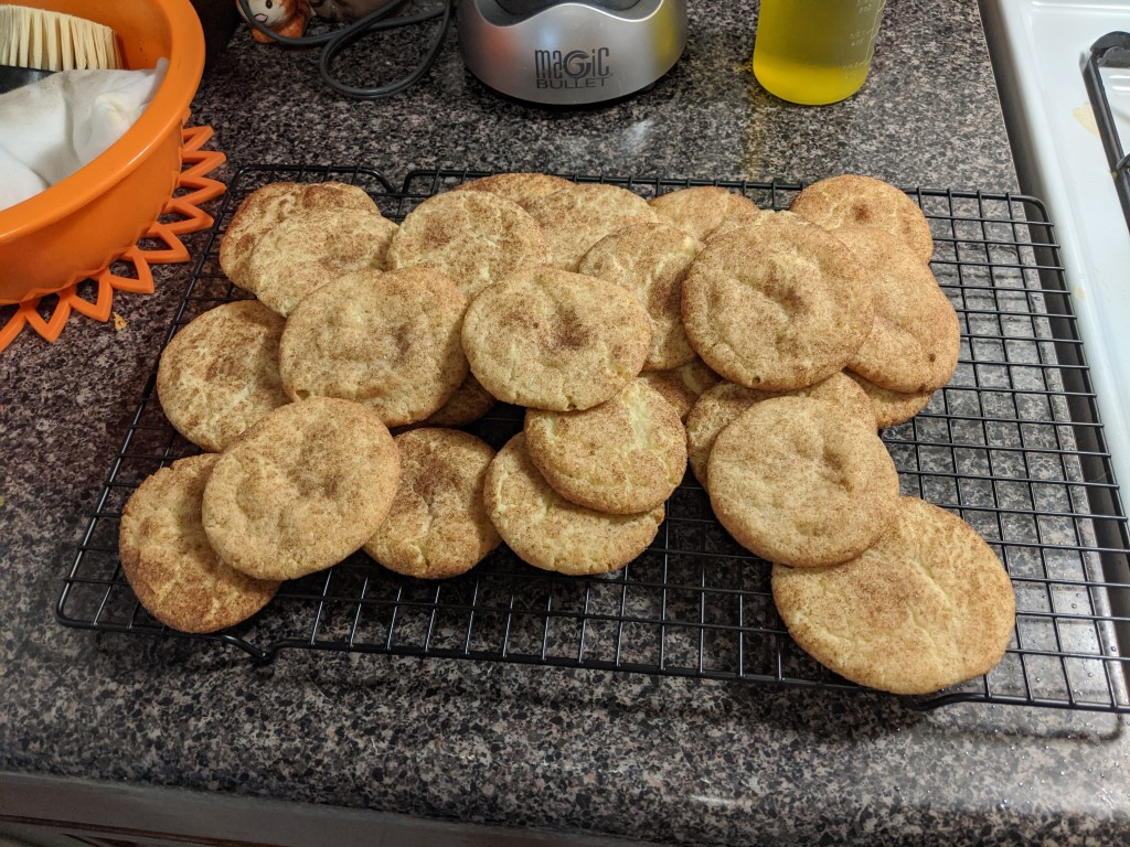 Fresh snickerdoodles cooling on a rack.