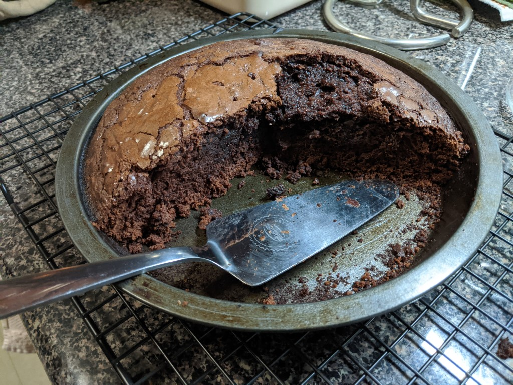 """A 9"""" round cake pan half filled with fresh baked brownie."""